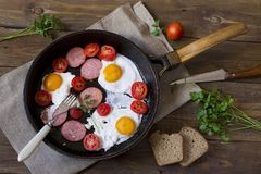 жаренные eggs and sausage with a tomato Stock Image