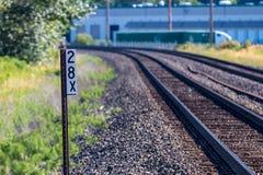 Железнодорожные пути и знак со зданием в расстоянии стоковое фото