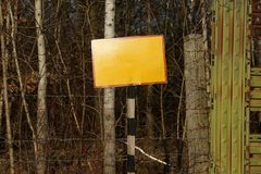 Желтая плита на striped столбце на загородке утюга и колючей проволоки стоковое фото
