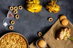 Желтые цветок, печенья и яблочный пирог лежа на серой предпосылке Плоское положение Взгляд сверху стоковое изображение