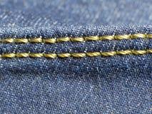 Желтый шов на брюках джинсов стоковое изображение rf