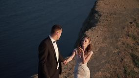 Жених и невеста идя на гору на заходе солнца сток-видео