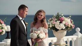 Жених и невеста на свадебной церемонии Молодая пара в стойках любов на своде Wedding морем акции видеоматериалы