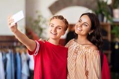 Женские друзья принимая selfie на магазин одежды стоковые изображения
