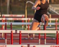 Женский бегун участвуя в гонке барьеры outdoors стоковое изображение rf
