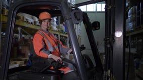 Женский водитель платформы грузоподъемника в трудных взглядах шлема и формы на камере и улыбках в складе видеоматериал