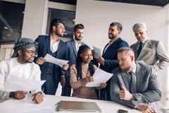 Женский ментор тренера разговаривая с менеджерами высшего звена в корпоративной тренировке в офисе стоковые фотографии rf