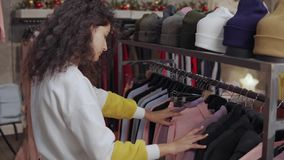 Женский покупатель выбирает теплую ультрамодную одежду в зале магазина сток-видео