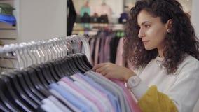 Женский покупатель магазина одежды моды ищет свитер на шкафе видеоматериал
