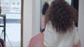 Женский покупатель принимает 2 одежды от шкафа и входит в раздевалку видеоматериал