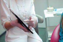 Женский дантист с терпеливой девушкой говоря на зубоврачебном офисе клиники стоковое фото