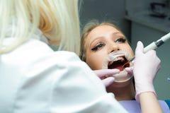 Женский доктор в форме проверяя вверх по зубам женского пациента в зубоврачебной клинике стоковое изображение rf