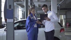 Женский специалист по автомобиля принимая данные об автомобиле для осмотра и молодого красивого человека кладя подпись в автомоби сток-видео