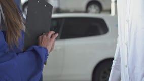 Женский специалист по автомобиля после принимать подписанные данные об автомобиле и принимающ ключ и трясущ руку молодого красиво акции видеоматериалы