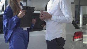 Женский специалист по автомобиля после принимать подписанные данные об автомобиле и принимающ ключ и трясущ руку молодого красиво видеоматериал