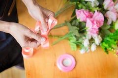 Женский флорист на работе используя аранжировать делая красивый искусственный жилет букета на цветочном магазине, деле, продаже и стоковое изображение rf