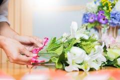 Женский флорист на работе используя аранжировать делая красивый искусственный жилет букета на цветочном магазине, деле, продаже и стоковые фотографии rf