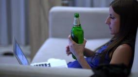 Женский работать на компьютере на софе, смотреть ТВ и выпивать пиво дома 4K акции видеоматериалы