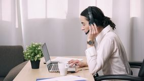 Женский работник центра телефонного обслуживания отвечает звонку клиента в офисе