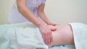 Женский masseur используя масло ароматности для массажировать брюшко женщины сток-видео