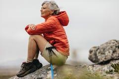 Женский trekker сидя на утесе ослабляя стоковые фото