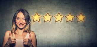 Женщина ¡ Ð heerful красивая усмехаясь показывающ большой палец руки вверх как жест выбирая оценку 5 звезд стоковое фото