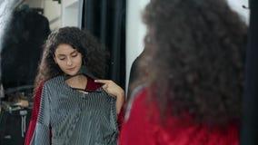 Женщина брюнета сравнивает 2 платья другого цвета в раздевалке в магазине акции видеоматериалы