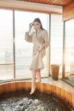 Женщина брюнета ослабляя в джакузи в спа-центре с панорамными окнами стоковые фотографии rf