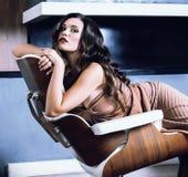 Женщина брюнет yong красоты сидя около камина дома, вечер зимы теплый в интерьере стоковые изображения rf
