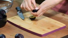 Женщина варя и режа сливу на деревянной разделочной доске подготовлять еды здоровый акции видеоматериалы
