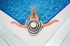 Женщина в бассейне соломенной шляпы расслабляющем стоковые изображения rf
