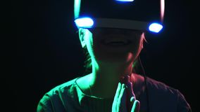 Женщина в больших пальцах руки шоу шлемофона VR вверх в неоновых светах видеоматериал