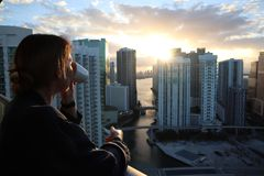 Женщина в купальном халате выпивая ее кофе или чай утра на городском балконе Красивый восход солнца в городском miami Женщина нас стоковая фотография rf