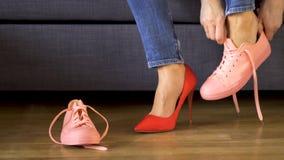 Женщина в джинсах принимает сексуальные красные пятки и кладет на удобные тапки коралла сток-видео