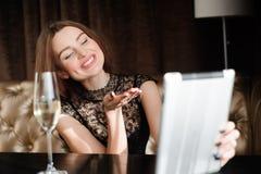 Женщина в ресторане ослабляя со стеклом ПК шампанского и планшета стоковое изображение