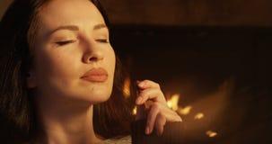 Женщина есть шоколад наслаждаясь вкусом чувствуя уютный и расслабленный с камином видеоматериал