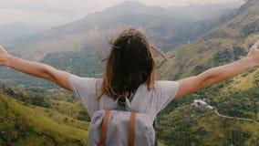 Женщина заднего взгляда конца-вверх возбужденная молодая туристская с оружиями отверстия рюкзака широко наблюдая эпичный пейзаж г видеоматериал
