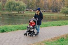 Женщина идет в парк с прогулочной коляской и небольшим ребенком около озера стоковые фото