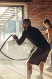 Женщина и человек в тренировке спортзала функциональной с работать веревочки сражения стоковые изображения rf