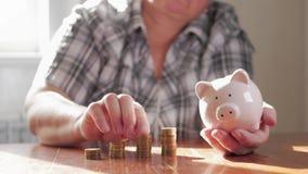 Женщина кладя монетку в копилку, сохраняя концепцию денег Будущие потребности одалживают образование или ипотечный кредит проводи видеоматериал