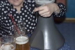 Женщина льет свежее холодное пиво от распределителя столешницы охлаждая в стекла пива стоковые фото