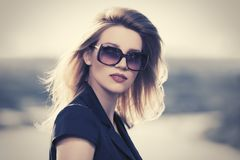 Женщина молодой моды белокурая в солнечных очках внешних стоковое изображение