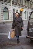 Женщина наслаждается успешными покупками, идя вниз по улице с сумками в ее руках стоковая фотография
