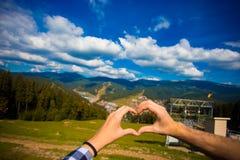 Женщина пар любовника Europen и природа перемещения человека рука в форме сердц С природой на горе стоковое изображение rf