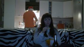 Женщина перед пивом напитков ТВ с обломоками, человек подготавливает еду стоковые изображения rf