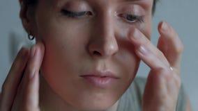 Женщина приглаживая и массажируя кожу, после применения учреждение на стороне видеоматериал