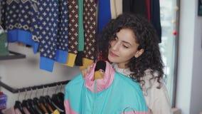 Женщина применяется к ее куртке тела 2 sportive в зале магазина, выбирая видеоматериал