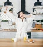 Женщина протягивая на кухне стоковые фотографии rf
