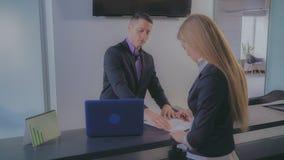 Женщина подписывает договор в банке стоковое фото