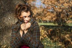 Женщина портрета крупного плана покрывая с курткой шотландки Зима холодно солнечний свет дуба пущи конструкции граници предпосылк стоковая фотография
